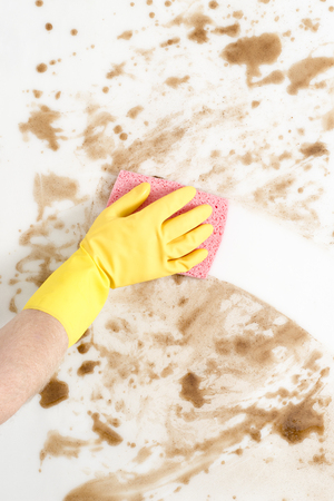 Gloved hand wiping a dirty counter top or floor with a pink sponge Imagens
