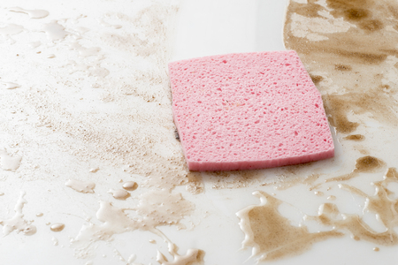 Pink sponge on a counter top or floow covered with spills