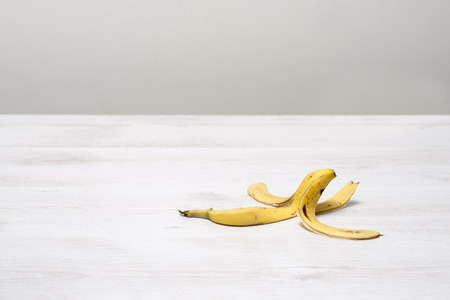 Banana peel on a white wooden surface with copy space