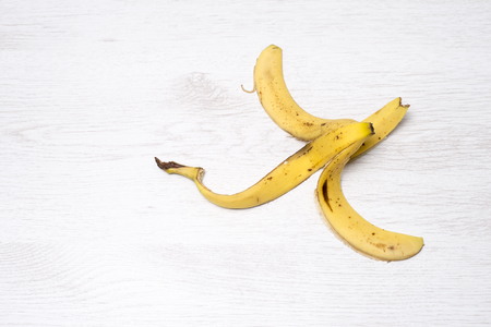Banana peel isolated on a white wooden background Imagens
