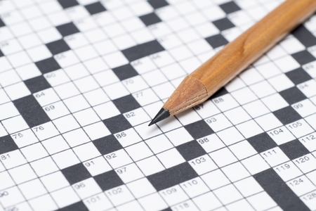 Close up of a pencil on an unanswered crossword puzzle