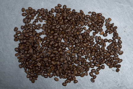 Overhead view of dark, roasted coffee beans on counter top
