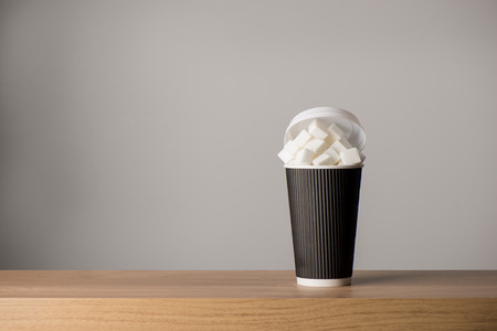 Tall paper coffee cup filled with sugar cubes on a wooden surface with copy space Imagens