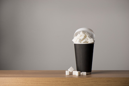 Tall paper coffee cup overflowing with sugar cubes on a wooden surface, copy space