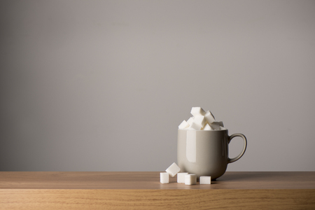 Ceramic coffee mug overflowing with sugar cubes, copy space