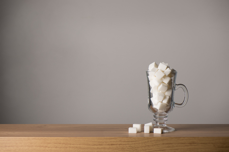 Latte glass overfilled with white sugar glass isolated on a wooden surface, copy space