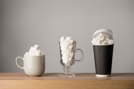 Coffee mug, latte glass, and tall paper cup all filled with sugar cubes Archivio Fotografico