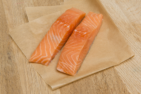 Two salmon slices on a wooden surface Imagens