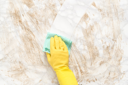 Hand wearing a glove, wiping clean a dirty marble counter or floor with a paper towel 免版税图像