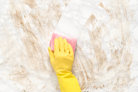 Gloved hand wiping clean a dirty marble floor or counter with a sponge 免版税图像