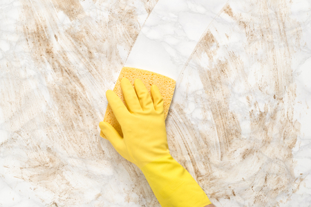 Gloved hand wiping clean a dirty marble counter or floor with a sponge
