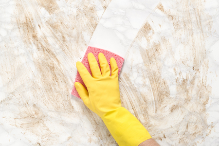 Hand wearing a glove wiping clean a dirty marble counter or floor with a sponge Imagens