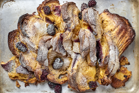 Overhead view of baked bread slices and cranberry sprinkled with confectioners sugar in a baking tray