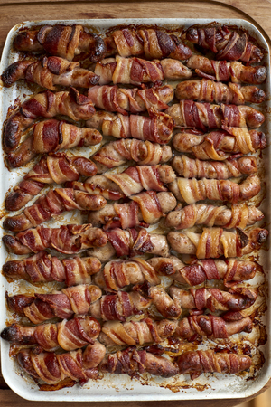 Overhead view of a tray of cooked pigs in blanket
