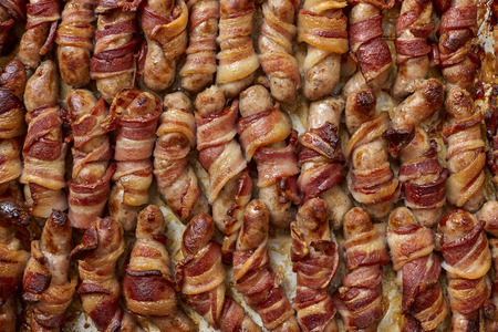 Cooked pigs in blanket or bacon wrapped sausages for backgrounds Imagens