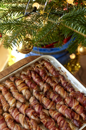 Tray of pigs in blankets beside a Christmas decor Imagens