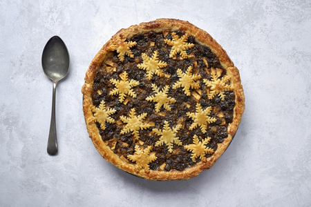 Overhead view of a large whole mince pie and a spoon
