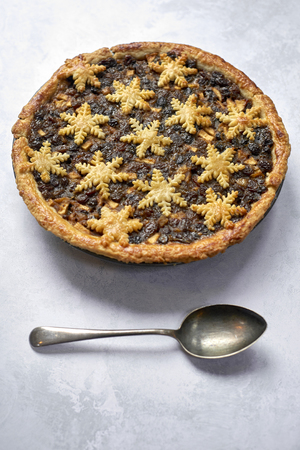 Large whole mince pie and a spoon, traditional British Christmas food