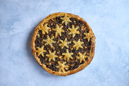 Large whole mince pie centered on blue stone background, traditional British Christmas food