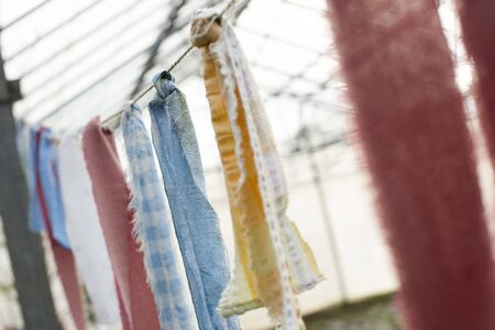 Close up of torn fabric strips tied to a wire with greenhouse in the background