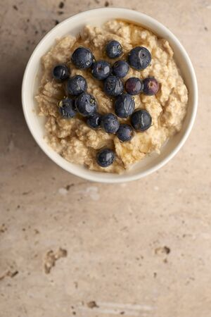 Overhead of a bowl of porridge with blueberries on top copy space