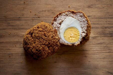 Scotch egg sliced in half, one half facing down and one half exposing the inside, on a wooden background