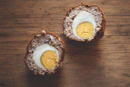 Scotch egg cut in half on wooden background 免版税图像