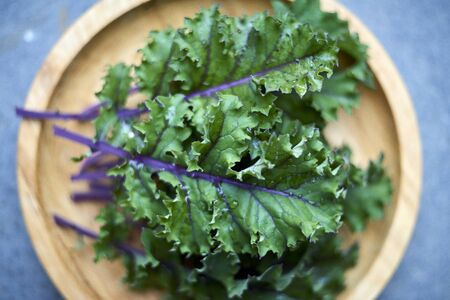 Focused closeup shot of red russian kale leaves on wooden plate 免版税图像