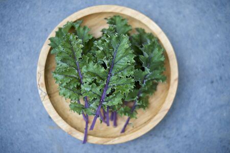Top view of red russian kale leaves on wooden dish over stone background 免版税图像