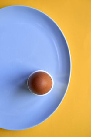 Top view of a brown egg in an egg cup on a blue plate over a yellow background