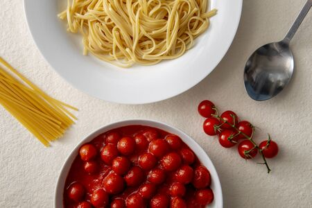 Plate of pasta or spaghetti and a bowl of tomato sauce overhead view surrounded by fresh tomatoes, raw pasta, and a spoon 免版税图像