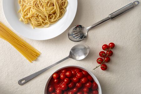 Stainless steel spoon and ladle between serving of pasta and bowl of tomato sauce 免版税图像