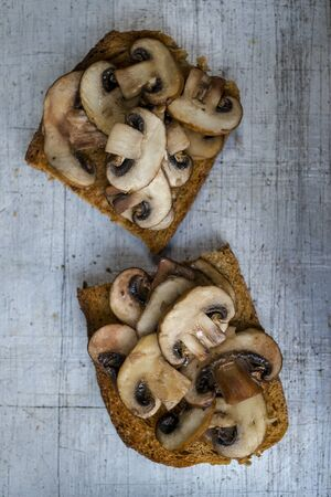 Mushrooms on toast slices on worn aluminum background overhead view