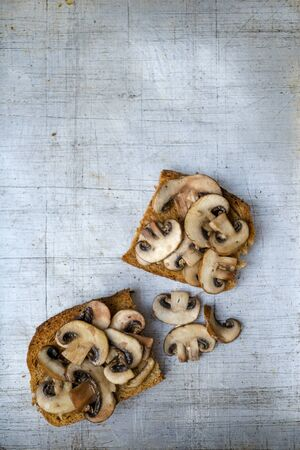 Mushrooms on toast servings on worn aluminum background overhead view with copy space