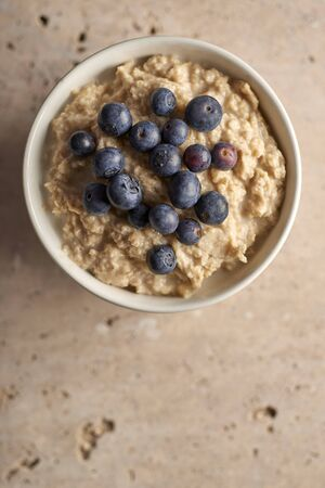 Top view of a bowl of oatmeal with blueberries on top copy space 免版税图像