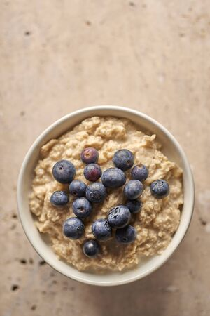 Overhead view of a bowl of oatmeal with blueberries on top copy space
