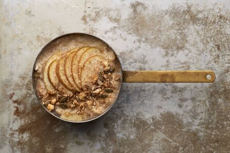 Oatmeal topped with apple slices and granola sprinkled with cinammon powder in copper pot overhead view