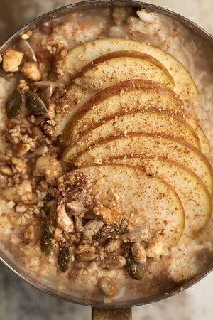 Close up of oatmeal topped with apple slices and granola sprinkled with cinammon in copper saucepan 免版税图像