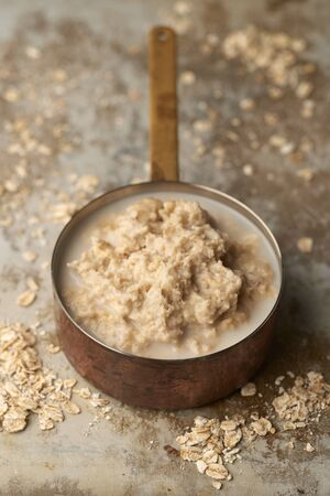 Porridge or oatmeal in a copper pot with scattered uncooked oats on worn stainless steel surface 免版税图像