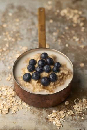 Porridge or oatmeal topped with blueberries in a copper pot with scattered uncooked oats on old stainless steel surface