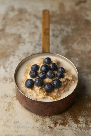 Porridge topped with blueberries in a copper pot on old stainless steel surface 免版税图像