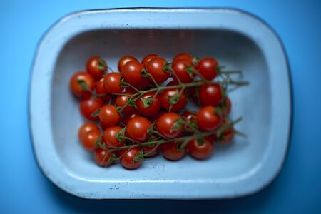 Top view of ripe cherry tomatoes in a light blue round rectangular deep dish over blue background