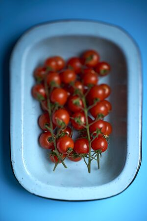 Top view of ripe cherry tomatoes attached to branches in a light blue round rectangular deep dish over blue background