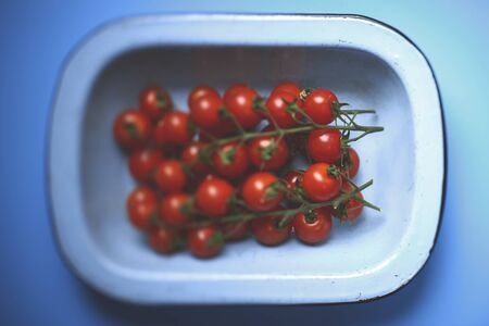 Overhead view of ripe cherry tomatoes in a light blue round rectangular deep dish over blue background