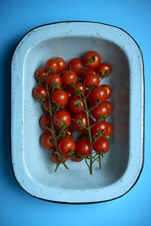Overhead view of ripe cherry tomatoes attached to branches in a light blue round rectangular deep dish over blue background 免版税图像