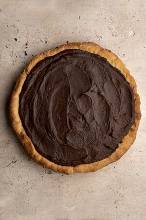 Overhead view of a dark chocolate pie or pudding pie on a stone background