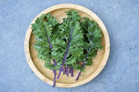 Red russian kale on wooden plate overhead shot framed at center over stone background