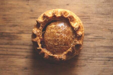 Top view of a meat pie framed at center on a wooden background