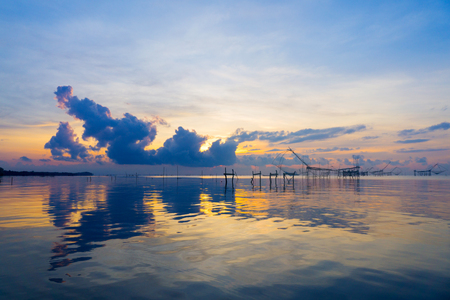 fish net: Seascape of sunrise with colorful sky at Pakpar, Pattalung, Southern of Thailand, reflection. Thai old traditional equipment style fishing trap make with bamboo frame and fish net dipping Stock Photo