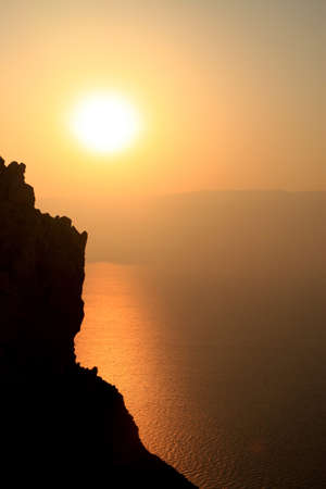 rising dead: Sunrise Over the Sea. The Sun is rising above the Dead Sea. A silhouette of a mountain side  is formed on the left. The Sun casts a long bright reflection on the sea below. Stock Photo